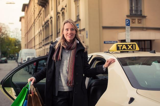 Młoda kobieta wychodzi z torby na zakupy taksówki Premium Zdjęcia