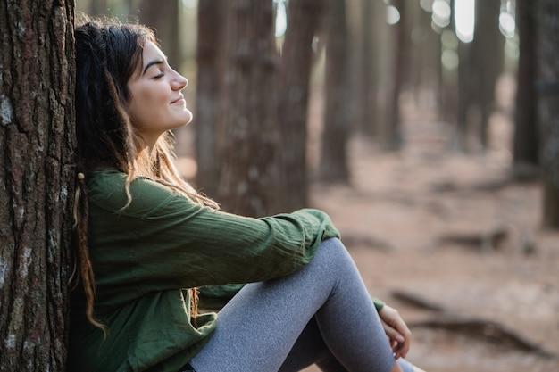 Młoda Kobieta Wycieczkowicz Relaksuje W Drewnach Premium Zdjęcia