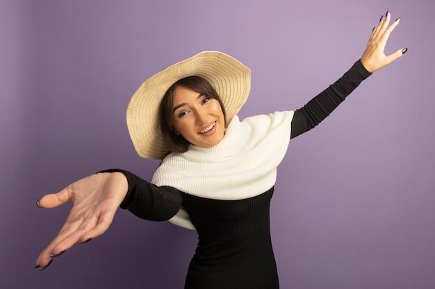 Młoda Kobieta Z Białym Szalikiem I Letnim Kapeluszem Szeroko Otwierającą Ręką, Czyniąc Powitalny Gest Darmowe Zdjęcia