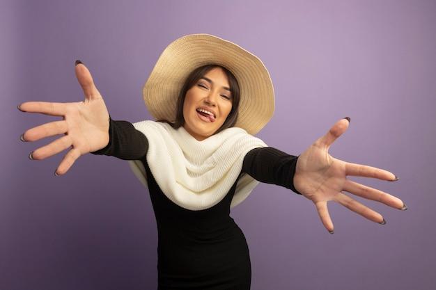 Młoda Kobieta Z Białym Szalikiem I Letnim Kapeluszem Szeroko Otwierające Się Ręce, Czyniąc Powitalny Gest Szczęśliwy I Wesoły Darmowe Zdjęcia