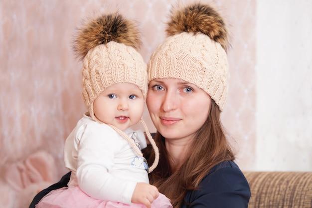 Młoda kobieta z córką w tych samych czapkach z dzianiny Premium Zdjęcia