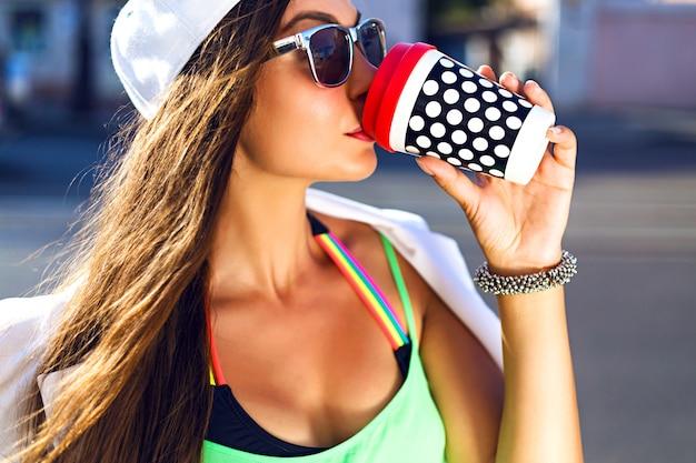 Młoda Kobieta Z Czapkę I Bez Okularów Do Picia Kawiarni Na Ulicy Darmowe Zdjęcia
