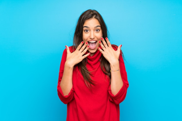 Młoda kobieta z czerwonym pulowerem odizolowywał błękit z niespodzianka wyrazem twarzy Premium Zdjęcia