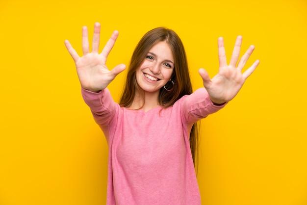 Młoda Kobieta Z Długie Włosy Nad Odosobnioną żółtą ścianą Liczy Dziesięć Z Palcami Premium Zdjęcia