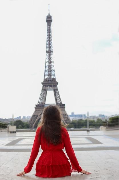 Młoda Kobieta Z Długimi Brązowymi Włosami W Czerwonej Sukience Siedzi Z Powrotem I Patrzy Na Wieżę Eiffla Premium Zdjęcia