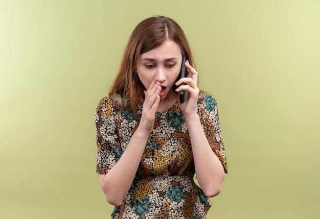 Młoda Kobieta Z Długimi Włosami Na Sobie Kolorową Sukienkę Rozmawia Przez Telefon Komórkowy Wstrząśnięty Stojąc Nad Zieloną ścianą Darmowe Zdjęcia