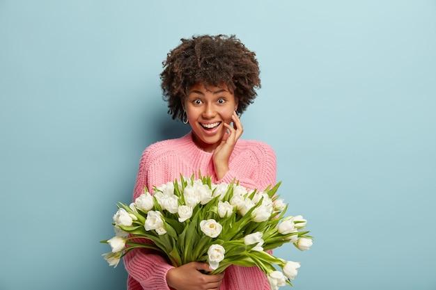 Młoda Kobieta Z Fryzurą Afro Trzymając Bukiet Białych Kwiatów Darmowe Zdjęcia