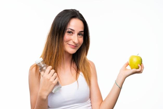 Młoda kobieta z jabłkiem nad odosobnioną biel ścianą Premium Zdjęcia