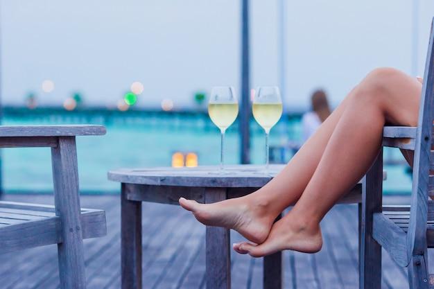 Młoda kobieta z kieliszkiem białego wina wieczorem Premium Zdjęcia