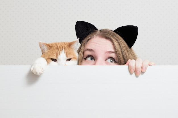 Młoda Kobieta Z Kotem Chuje Się Za Biały Sztandar Premium Zdjęcia