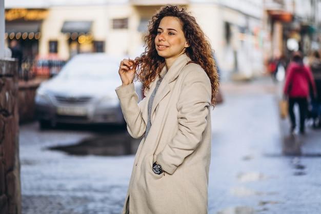 Młoda kobieta z kręconymi włosami poza ulicą Darmowe Zdjęcia