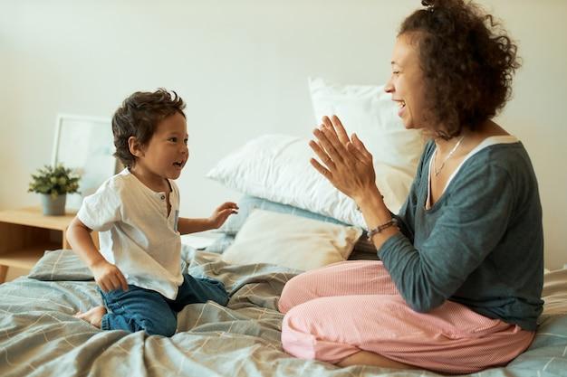 Młoda Kobieta Z Kręconymi Włosami Siedzi Na łóżku Z Uroczym Synem Darmowe Zdjęcia