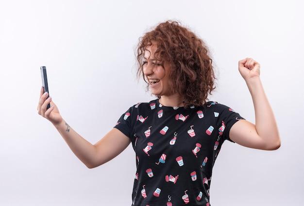 Młoda Kobieta Z Krótkimi Kręconymi Włosami Trzyma Smartfon Zaciskając Pięść Szczęśliwa I Podekscytowana, Ciesząc Się Swoim Sukcesem Stojącym Nad Białą ścianą Darmowe Zdjęcia
