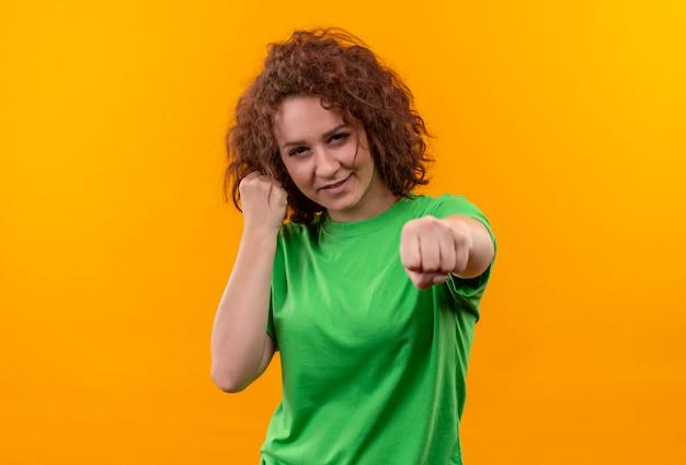 Młoda Kobieta Z Krótkimi Kręconymi Włosami W Zielonej Koszulce Zaciskając Pięść, Udając Boksera Stojącego Nad Pomarańczową ścianą Darmowe Zdjęcia