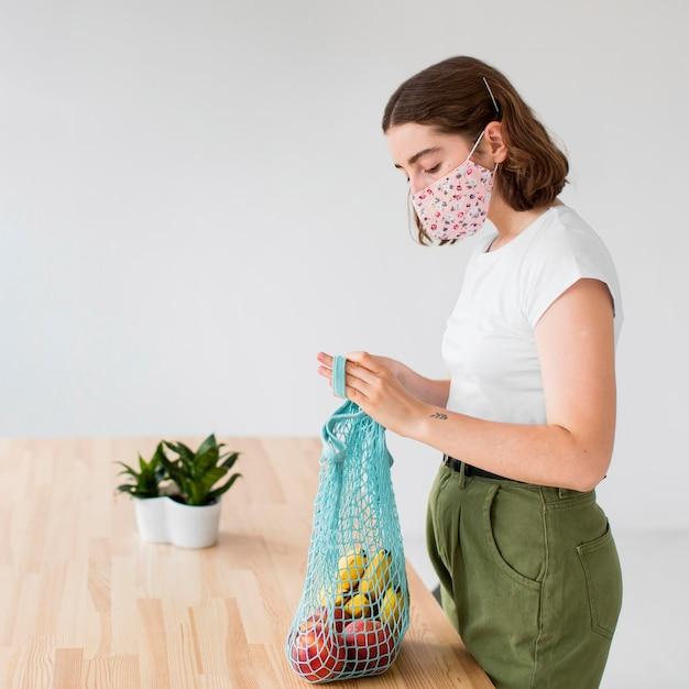 Młoda Kobieta Z Maską Biorąc Artykuły Spożywcze Z Torby Darmowe Zdjęcia