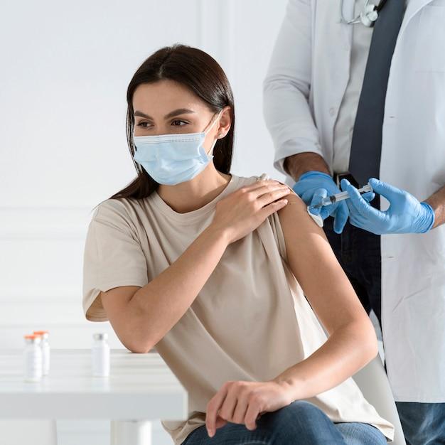 Młoda Kobieta Z Maską Medyczną Jest Szczepiona Przez Lekarza Darmowe Zdjęcia
