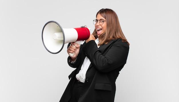 Młoda Kobieta Z Megafonem Czuje Się Szczęśliwa, Pozytywna I Odnosząca Sukcesy, Zmotywowana, Gdy Staje Przed Wyzwaniem Lub świętuje Dobre Wyniki Premium Zdjęcia