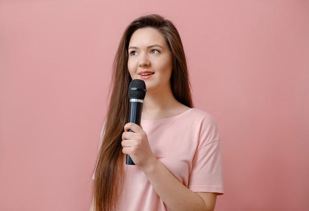Młoda Kobieta Z Mikrofonem W Ręku Na Różowo Premium Zdjęcia
