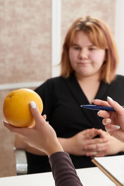 Młoda Kobieta Z Nadwagą Odwiedza Dietetyka, Aby Schudnąć Przy Pomocy Diety. Premium Zdjęcia