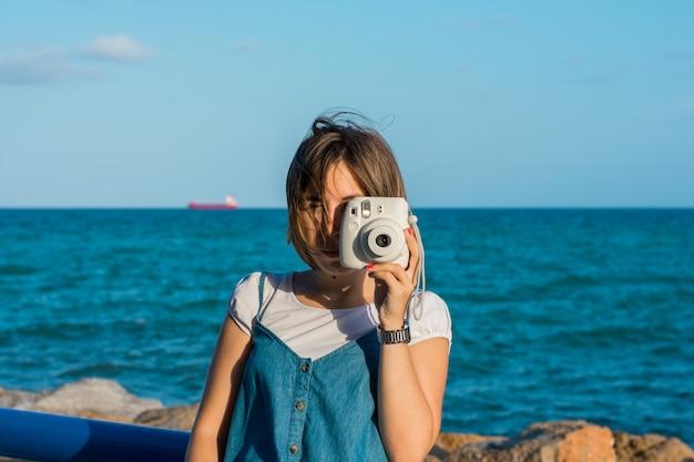 Młoda kobieta z natychmiastową kamerą na wybrzeżu Premium Zdjęcia
