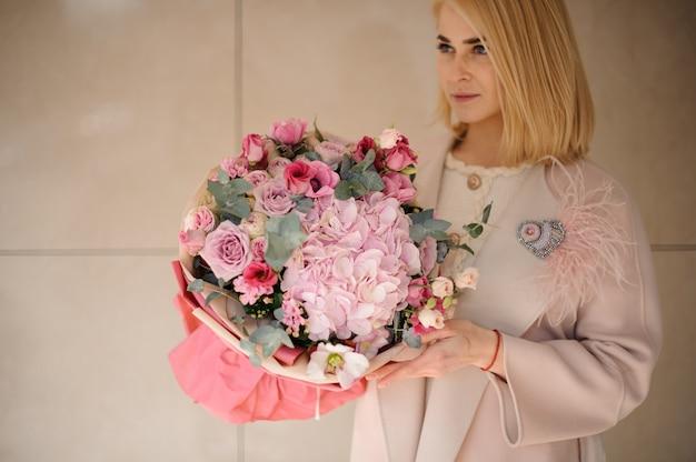 Młoda kobieta z niesamowitym bukietem kwiatów Premium Zdjęcia