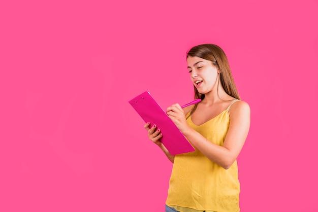 Młoda kobieta z pastylką dla papieru na różowym tle Darmowe Zdjęcia