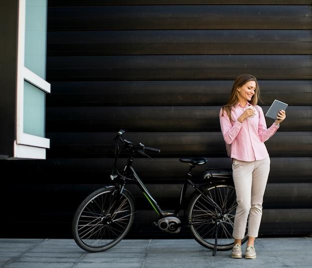 Młoda kobieta z pastylką i rowerem plenerowymi Premium Zdjęcia