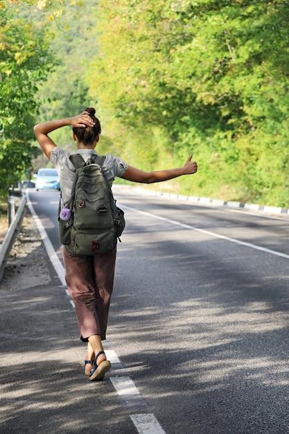 Młoda Kobieta Z Plecakiem Próbuje Zatrzymać Przejeżdżający Samochód Do Autostopu Premium Zdjęcia