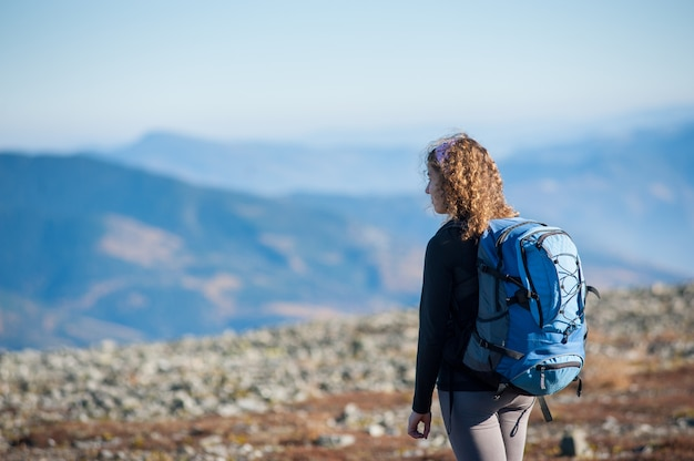 Młoda kobieta z przyrodą na wycieczkę z plecakiem w górach Premium Zdjęcia