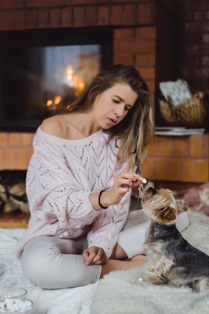 Młoda kobieta z psem przy kominku pije kakao z pianką. Darmowe Zdjęcia