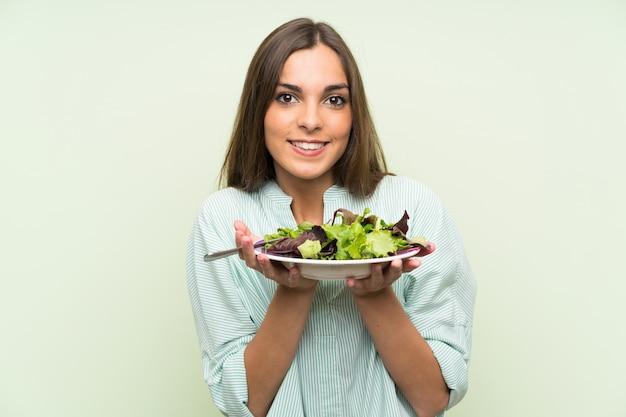 Młoda kobieta z sałatką nad odosobnioną zieleni ścianą Premium Zdjęcia