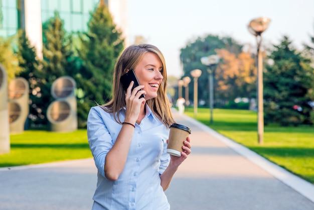 Młoda kobieta z smartphone chodzenia na ulicy, śródmieściu. w tle zamazana jest ulica, patrząc z przodu Darmowe Zdjęcia