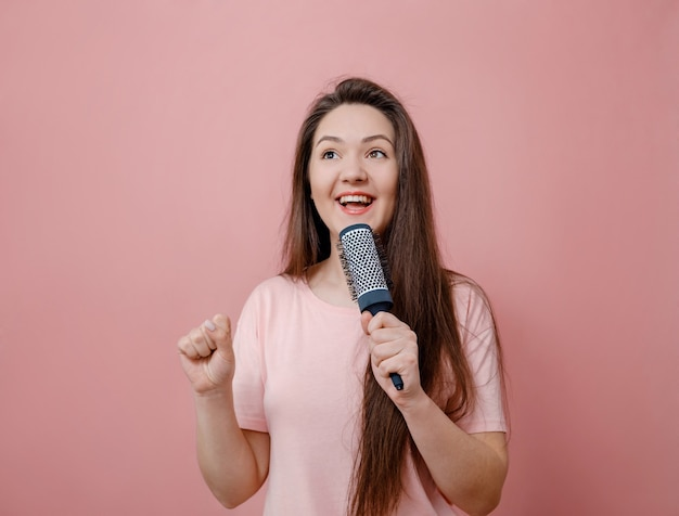 Młoda Kobieta Z Szczotką Do Włosów Jak Z Mikrofonem W Ręku Na Różowym Tle Premium Zdjęcia