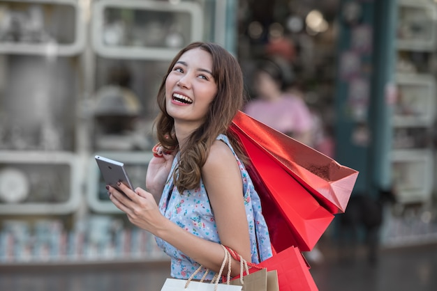 Młoda kobieta z torba na zakupy i smartphone w jej ręce przy centrum handlowym. Premium Zdjęcia