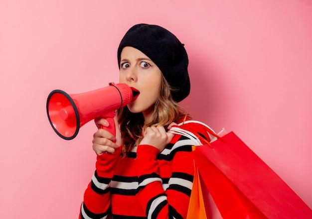Młoda kobieta z torby na zakupy i głośnik na różowej ścianie Premium Zdjęcia
