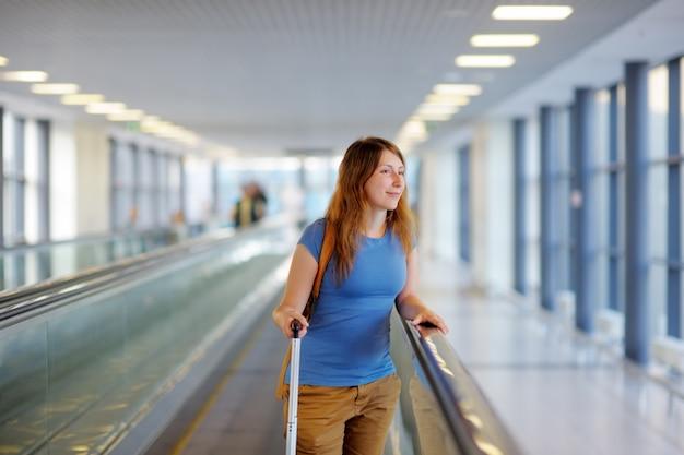 Młoda Kobieta Z Walizką Na Lotnisku Premium Zdjęcia
