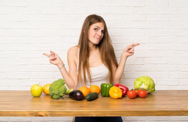 Młoda Kobieta Z Wiele Warzywami Wskazuje Laterals Ma Wątpliwości Premium Zdjęcia
