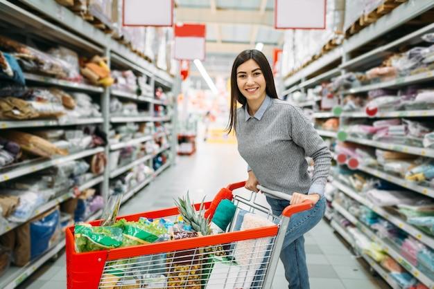 Młoda Kobieta Z Wózkiem Pełnym Towarów W Supermarkecie, Zakupy. Kobieta Klient W Sklepie, Kupujący Na Rynku Premium Zdjęcia