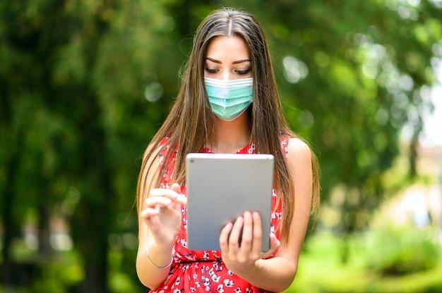 Młoda Kobieta Za Pomocą Cyfrowego Tabletu Siedzi Na ławce W Parku I Nosi Maskę, Koncepcja Koronawirusa Premium Zdjęcia
