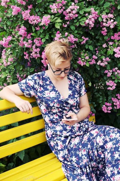 Młoda Kobieta Za Pomocą Smartfona W Pobliżu Krzewu Kwiatowego Premium Zdjęcia