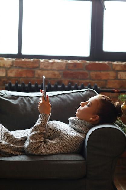 Młoda Kobieta Za Pomocą Tabletu Na Kanapie Darmowe Zdjęcia