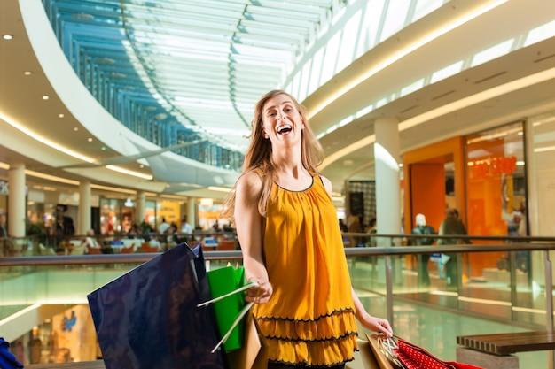 Młoda kobieta zakupy w centrum handlowym z torbami Premium Zdjęcia