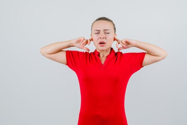 Młoda Kobieta Zatykająca Uszy Palcami W Czerwonej Koszulce I Wyglądająca Na Zirytowaną Darmowe Zdjęcia