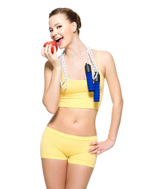 Młoda Kobieta Ze Zdrową Sportową Sylwetką, Jedzenie Czerwonego Jabłka Z Skakanką Na Szyi Darmowe Zdjęcia