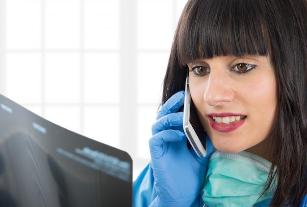 Młoda kobiety lekarka patrzeje pacjentów promieniowanie rentgenowskie i dzwonić Premium Zdjęcia