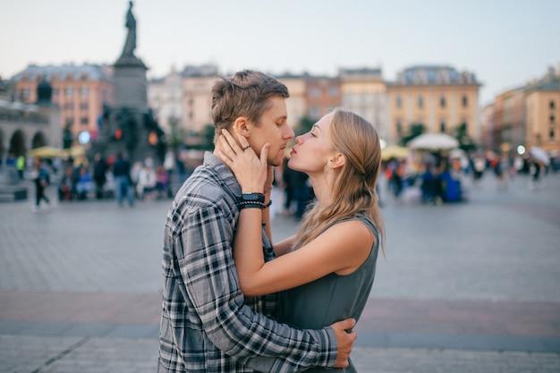 Młoda kochająca para ściska się na centralnym placu w krakowie Premium Zdjęcia
