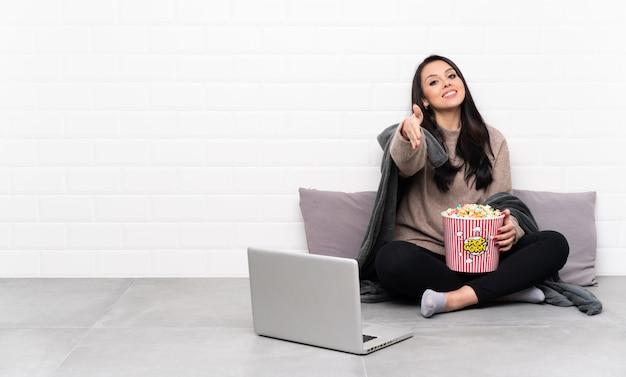 Młoda Kolumbijska Dziewczyna Trzyma Miskę Popcornu I Pokazuje Film W Laptopie, ściskając Dłonie Za Zamknięcie Dobrego Interesu Premium Zdjęcia