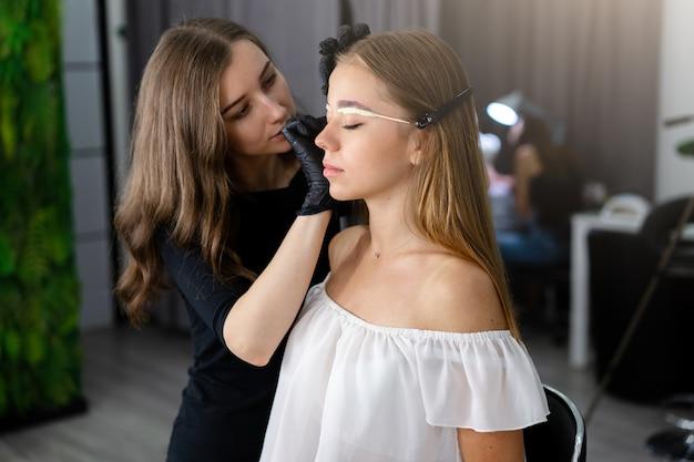 Młoda Kosmetyczka Dziewczynka Kaukaski Posiada Model Korekcji Brwi Premium Zdjęcia
