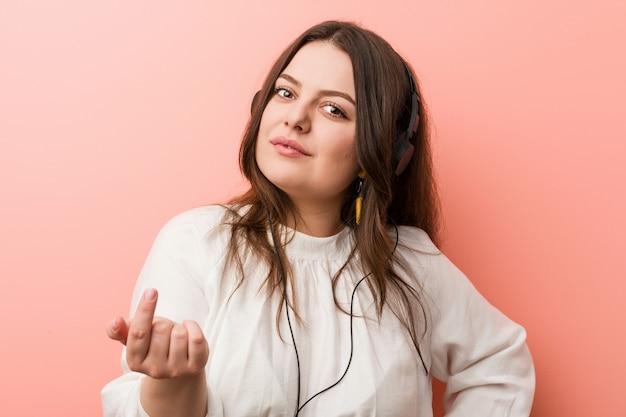 Młoda, kręcona kobieta w dużych rozmiarach, słuchająca muzyki ze słuchawkami wskazującymi na ciebie palcem, jakby zachęcając, podejdź bliżej. Premium Zdjęcia