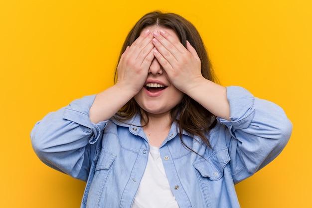 Młoda, kręcona kobieta w dużych rozmiarach zakrywa oczy dłońmi, uśmiecha się szeroko, czekając na niespodziankę. Premium Zdjęcia